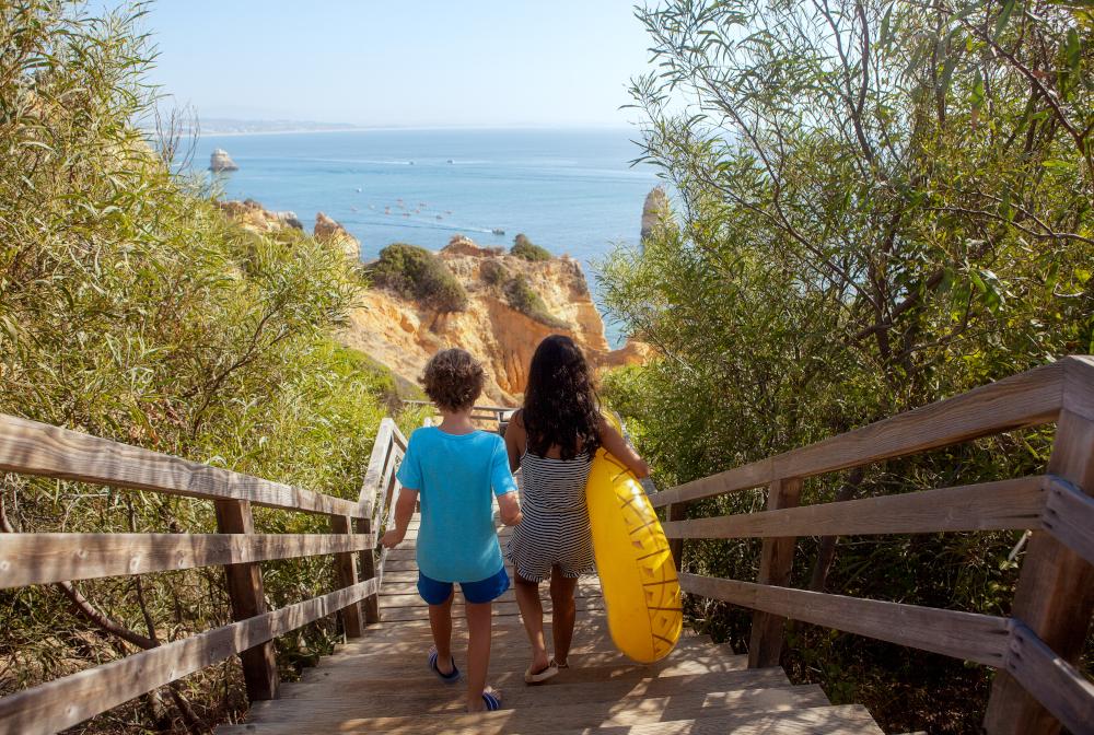 Two Kids Walking Down To Beach.rear View